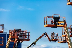 A group of raised aerial lifts, work platforms, are seen in an elevated state in storage, hydraulic mobile cranes with copy space